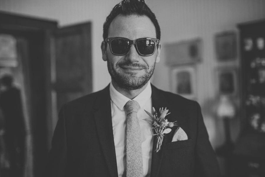 The groom smiles at the camera