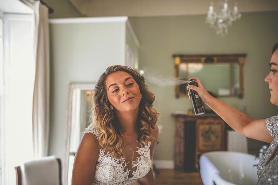 The bride has her hair sprayed by her friend