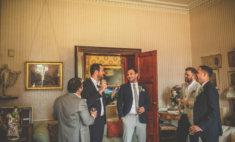 The groom and his ushers share a joke and enjoy a drink before the outdoor ceremony at Pennard house, Somerset