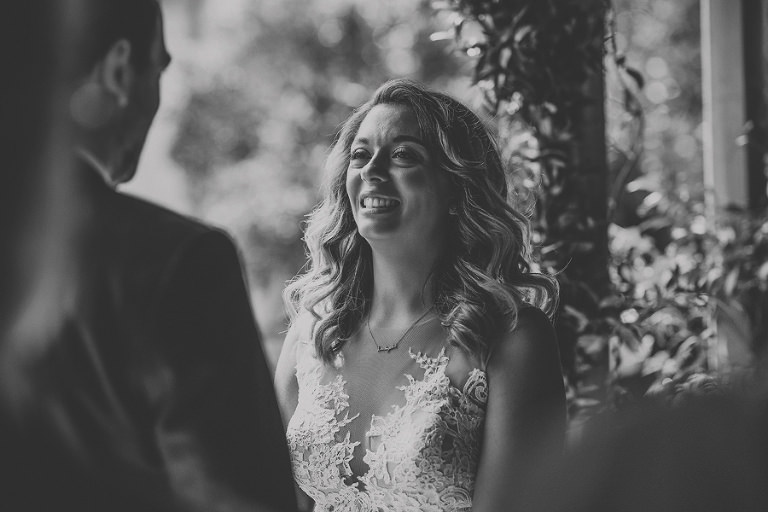 The bride smiles at the groom during the outdoor ceremony at Pennard house, Somerset