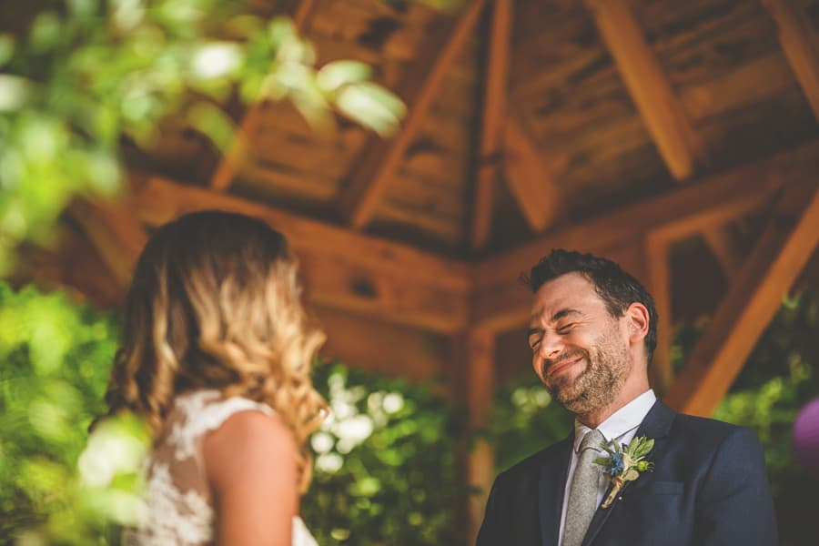 The groom laughs with the bride at the outdoor ceremony at Pennard house, Somerset