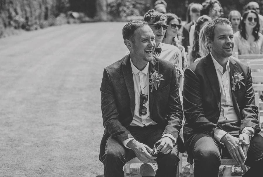 The brides brother laughs at a joke during the outdoor ceremony