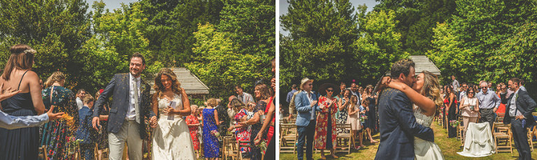 The bride and groom walk down the aisle of the outdoor ceremony at Pennard house, Somerset
