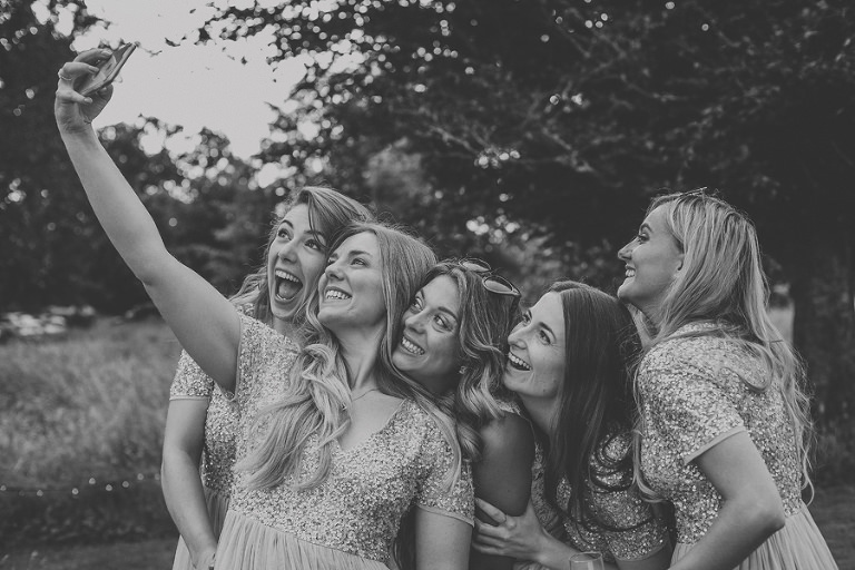 The bride and the bridesmaids taking a selfie at Pennard house, Somerset