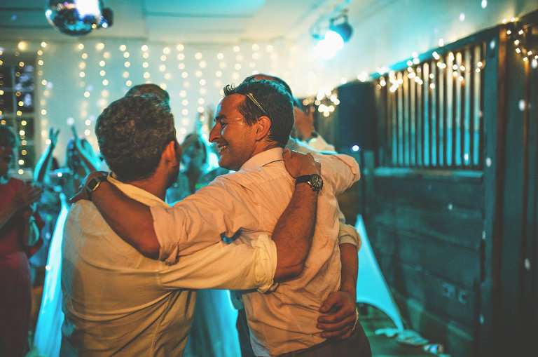Wedding guests embrace each other during the evening celebrations
