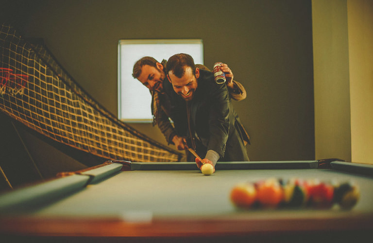 The groom and his best man share a joke on the pool table