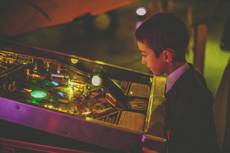 A boy playing pinball