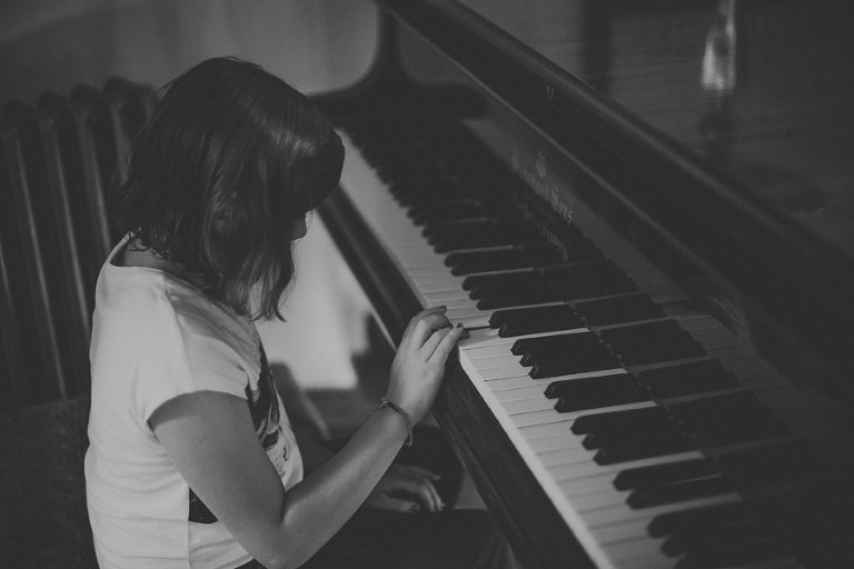 A girl plays the piano at Voewood, Norfolk
