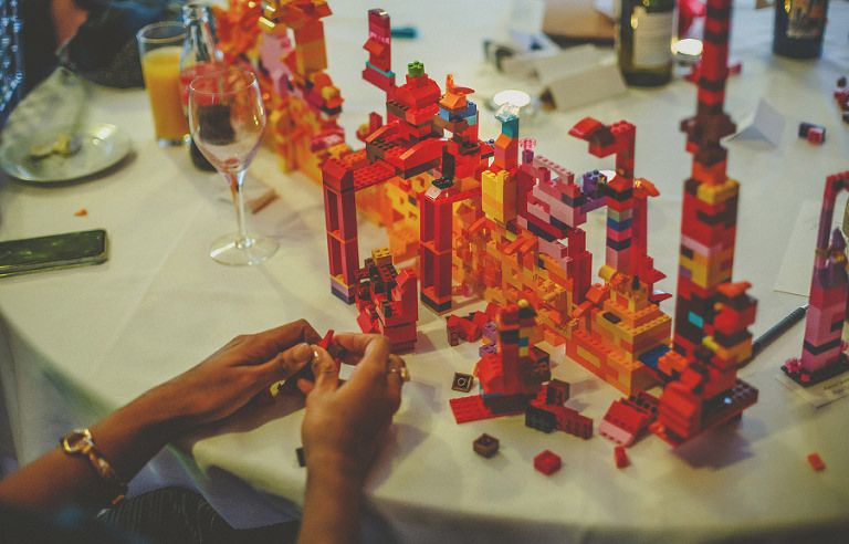 A wedding guest builds lego on the table