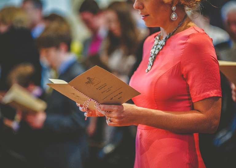 The brides sister looks through the church order of hymns