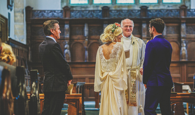 The wedding couple share a joke with the vicar at the Church of St Michael and All Angels, Somerton