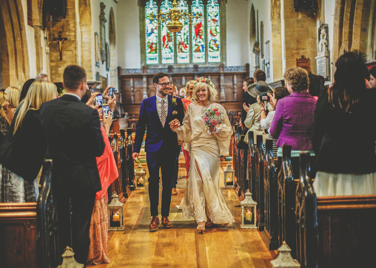 The bride and groom walk down the aisle of the Church of St Michael and All Angels, Somerton