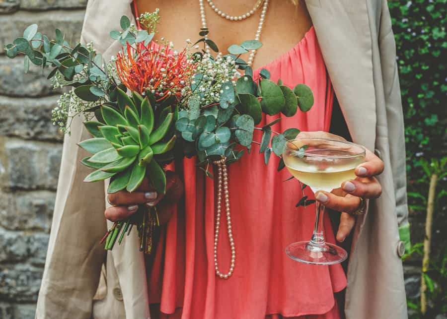A bridesmaid holds her flowers and a glass of champagne