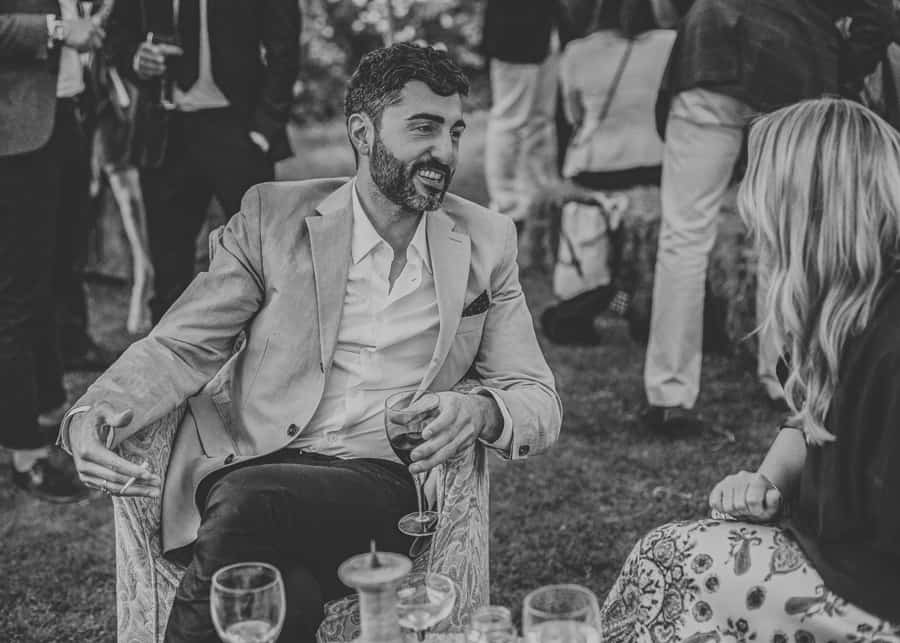 A wedding guest sat with a glass of wine talks to a friend of the bride and groom