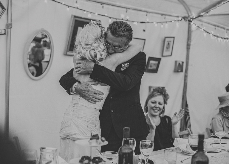 The brides father stands up and embraces his daughter in the marquee at Sharpham Park