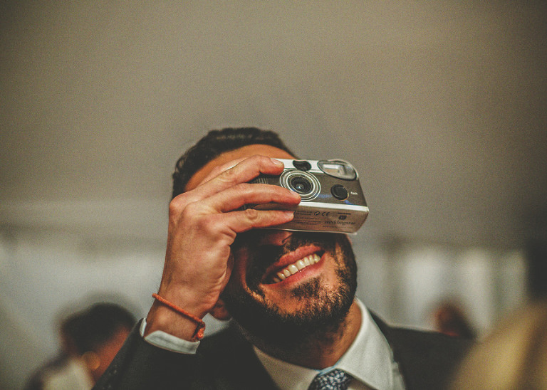 A member of the wedding party holds up a camera