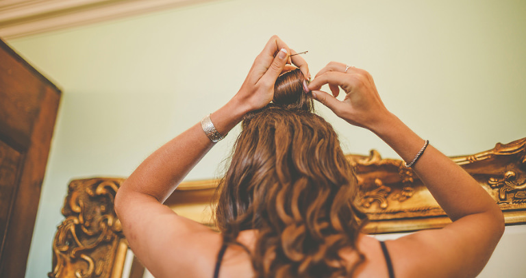 A bridesmaid taking rollers out of her hair