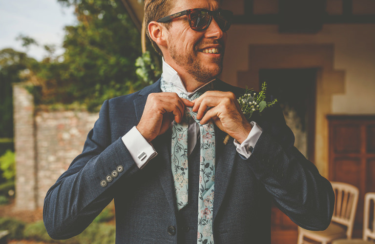 The groom gets ready outside in the gardens at Barley Wood house, Bristol