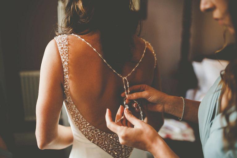 A bridesmaid ties the back of the brides dress at Barley Wood house, Bristol