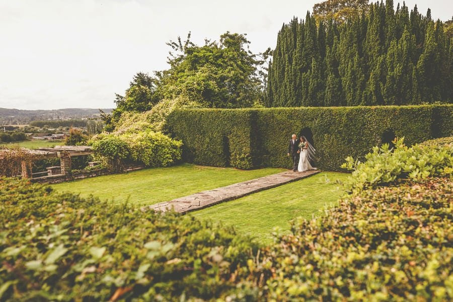 The bride and her father enter the gardens at Barley Wood house, Bristol