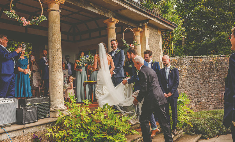 The bride walks up the steps to meet the groom