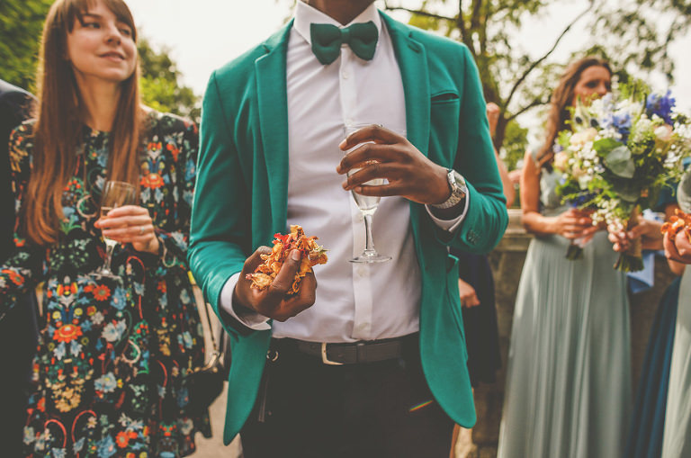 A wedding guest holding confetti and a glass of champagne