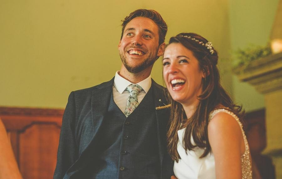 The bride and groom laugh at jokes being told by the best men at Barley Wood house, Bristol