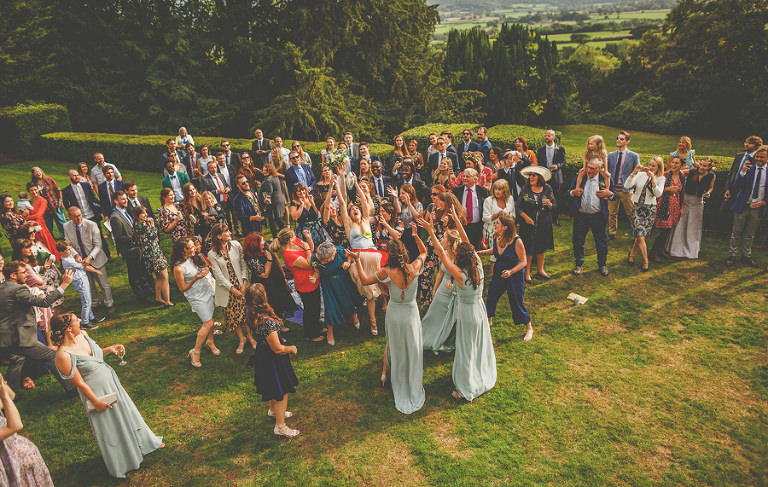 Catching the bouquet in the back garden at Barley Wood house, Bristol