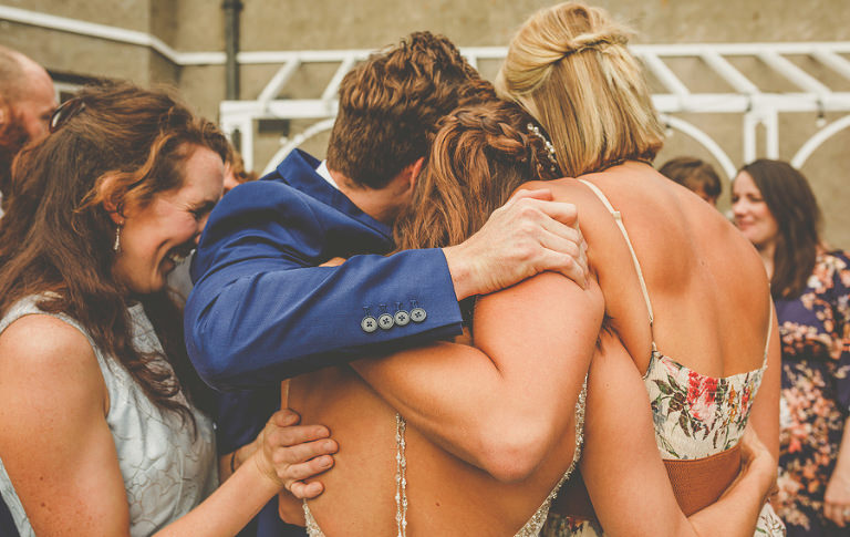 Friends give the bride a hug in the back garden at Barley Wood house, Bristol