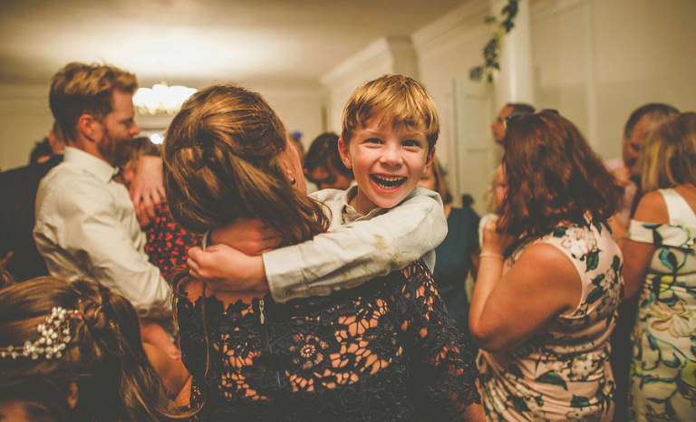 A boy laughs on the dancefloor with his mother