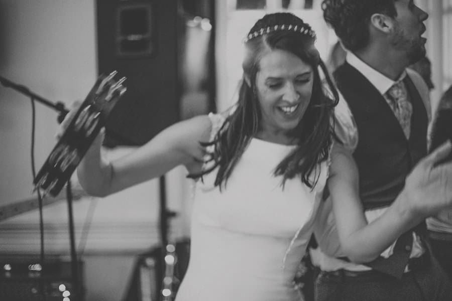 The bride plays a tambourine on the dancefloor