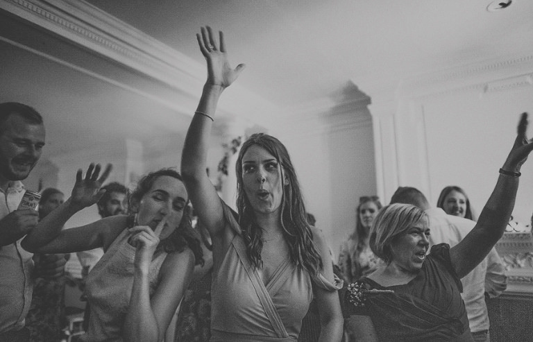 The brides sister sings and holds her arm in the air