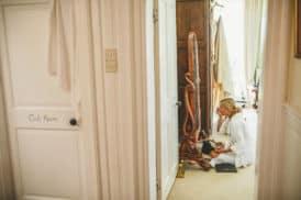 A bridesmaid gets ready at Pennard house, Somerset