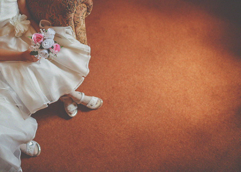 The flowergirls sit on a sofa and wait for the bride