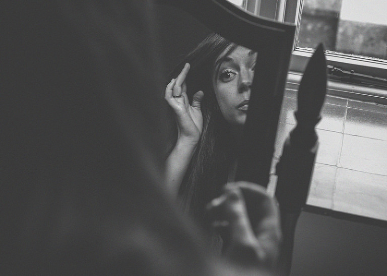A bridesmaid looks into the mirror and straightens her hair