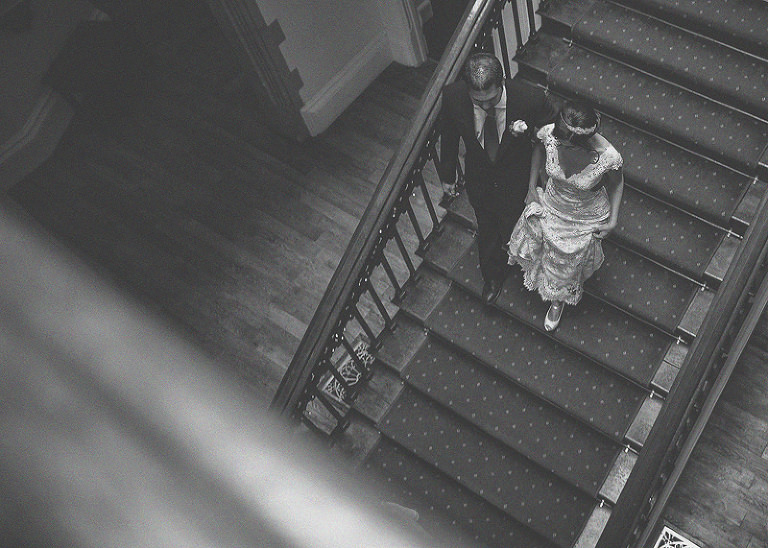 The bride and her brother walk down the staircase at St. Audries Park