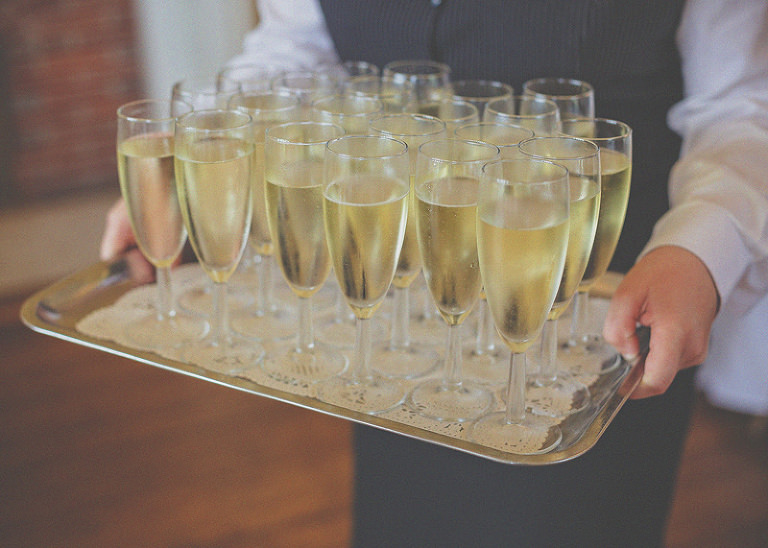 A tray of champagne flutes filled with champagne held by a waiter