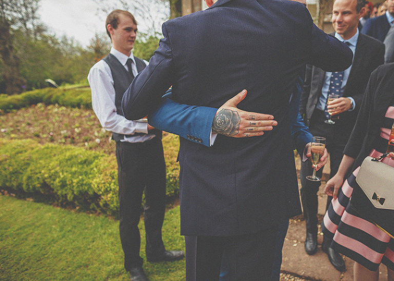 A wedding guest places his arm around the groom outside the orangery