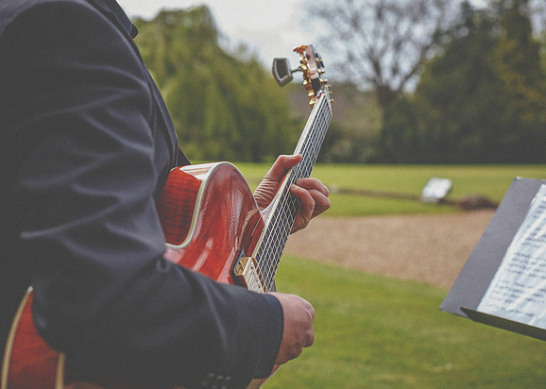 A member of the wedding band plays guitar outside the orangery