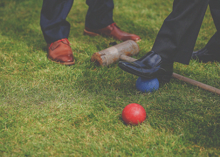 A wedding guest puts his foot on a croquet ball on the lawn at St. Audries Park