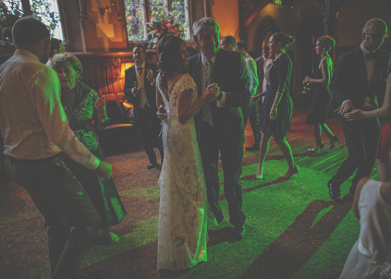 The bride dances with a wedding guest on the dancefloor at St. Audries Park