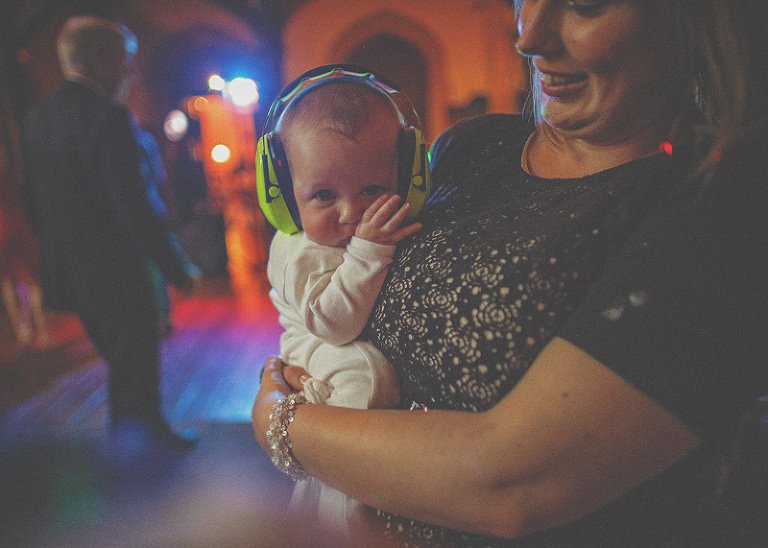 A baby with ear muffs is held by her mother