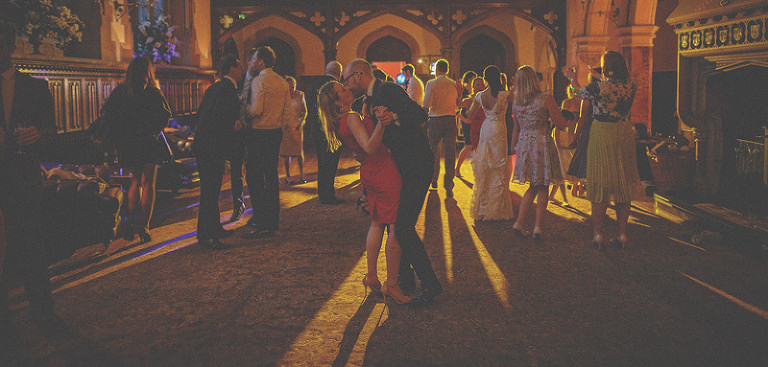 Wedding guests dance and kiss each other on the dancefloor