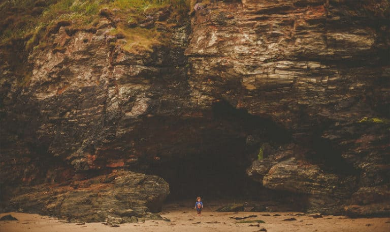 A little boy stands outside a cave on a beach in St. Ives