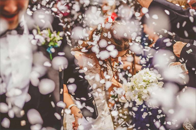 Confetti covers the bride and groom as they leave the church