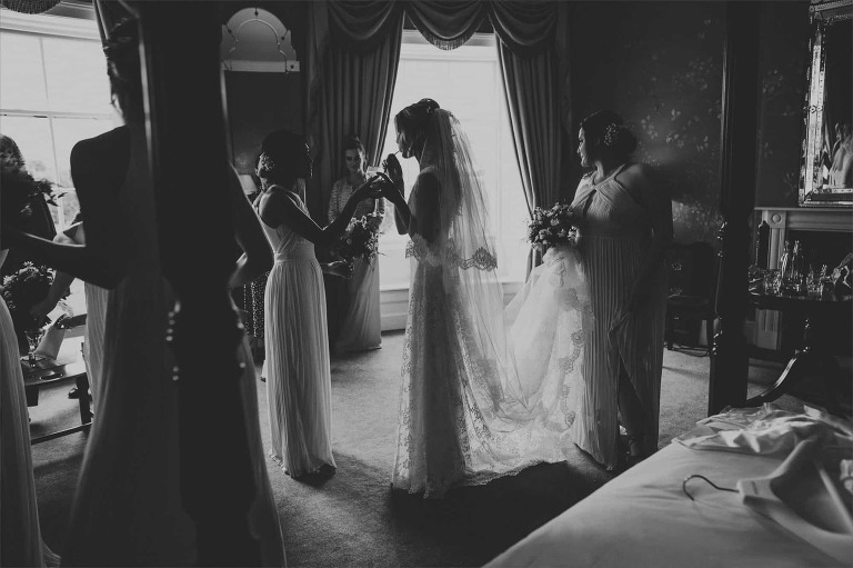 Bridal party getting ready while the bride sips a cocktail