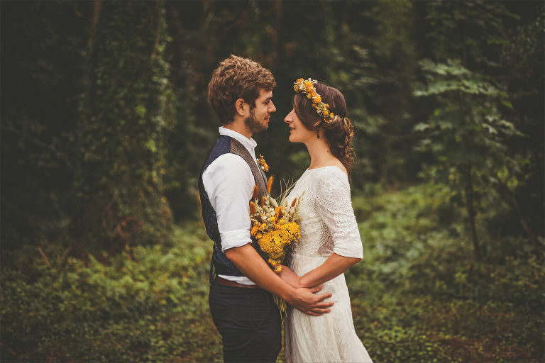 A bride and groom look into each others eyes and hold each other in a forest