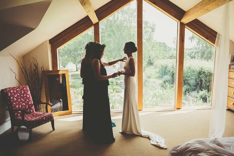 Bridesmaids help the bride get ready in her parents bedroom