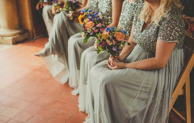 Bridesmaids sat on wooden chairs holding their bouquets