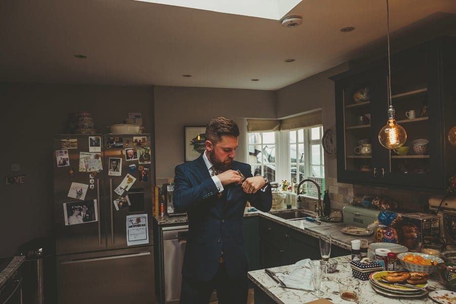 A man places a handkerchief into the top pocket of his suit jacket in the kitchen